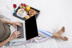 Petit déjeuner d'ordinateur portable de lit de femme Image stock