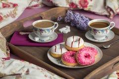 Petit déjeuner dans le lit avec du café et des butées toriques Photo stock