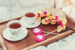 Petit déjeuner dans le lit dans le jour de valentines Tasse de sucreries de thé et de bonbon Concept d'amour ou de vacances Image stock