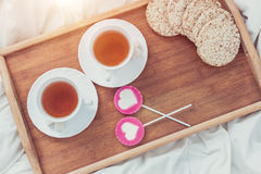 Petit déjeuner dans le lit dans le jour de valentines Tasse de sucreries de thé et de bonbon Concept d'amour ou de vacances Image libre de droits