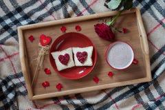 Petit déjeuner dans le lit pour le jour de valentines Présent romantique avec la fleur rose, les pains grillés et le chocolat cha Images libres de droits
