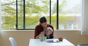 Petit déjeuner de alimentation de mère à son bébé 4k banque de vidéos
