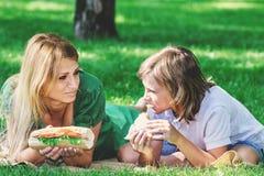 Petit déjeuner de famille sur l'herbe Maman et fils mangeant le sandwich Image stock
