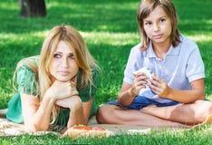 Petit déjeuner de famille sur l'herbe Maman et fils mangeant le sandwich Photo stock