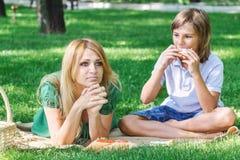 Petit déjeuner de famille sur l'herbe Maman et fils mangeant le sandwich Image libre de droits