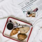 Petit déjeuner de journal d'expresso d'Americano de café dans le concept de lit Photos stock