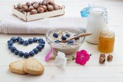 Petit déjeuner de l'amour des myrtilles de farine d'avoine avec les coeurs, le miel, les écrous et le lait Photographie stock libre de droits
