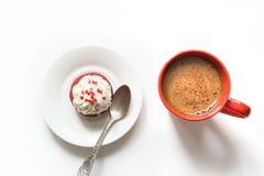 Petit déjeuner de matin avec la tasse du café noir et du petit gâteau rouge de velours sur le blanc Vue supérieure Photos stock
