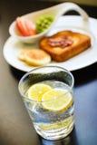 Petit déjeuner de matin avec le citron étincelant l'eau Photographie stock libre de droits