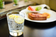 Petit déjeuner de matin avec le citron étincelant l'eau Photo stock