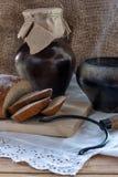 Petit déjeuner de pays - pain coupé en tranches, un pot de cuisson à la vapeur et une cruche sur la table en bois Photos stock
