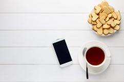 Petit déjeuner de tasse de thé et biscuits et smartphone en forme de coeur faits maison sur la table en bois blanche Photo libre de droits