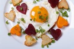 Petit déjeuner des coeurs romantiques frits des légumes et des oeufs Image stock
