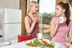 Petit déjeuner deux appréciant femelle à la maison ensemble Photo stock