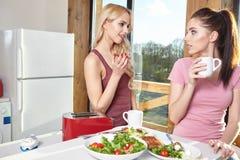 Petit déjeuner deux appréciant femelle à la maison ensemble Images libres de droits