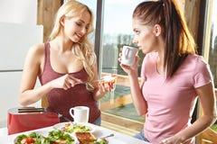 Petit déjeuner deux appréciant femelle à la maison ensemble Image libre de droits