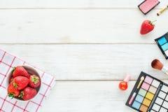 Petit déjeuner et cosmétiques féminins sur une table blanche Image stock