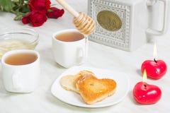 Petit déjeuner facile pour le jour du ` s de Valentine avec en deux pièces du pain, du miel et du thé Photo stock