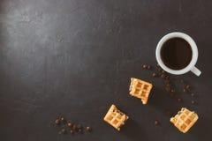 Petit déjeuner fait maison, table noire en pierre Morceaux cassés de gaufres viennoises, une tasse de café, grains de café disper photo stock