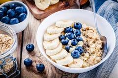 Petit déjeuner : farine d'avoine avec des bananes, des myrtilles, des graines de chia et des amandes photographie stock libre de droits