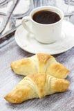 Petit déjeuner français : croissant et café Photos stock