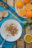 Petit déjeuner, fruit, flocons d'avoine, lait et jus d'orange sains sur la table en bois Photographie stock libre de droits