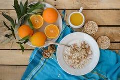 Petit déjeuner, fruit, flocons d'avoine, lait et jus d'orange sur la table en bois Images stock