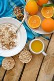 Petit déjeuner, fruit, flocons d'avoine, lait et jus d'orange sur la table en bois Photos libres de droits