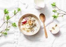 Petit déjeuner gratuit de gluten - quinoa, lait de noix de coco, banane, pomme, bol de beurre d'arachide sur le fond clair, vue s images stock
