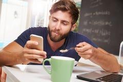 Petit déjeuner mangeur d'hommes tout en à l'aide du téléphone portable et de l'ordinateur portable photo stock