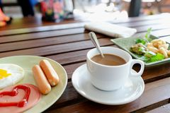 Petit déjeuner, oeufs, saucisses, jambon et café noir image stock