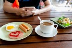 Petit déjeuner, oeufs, saucisses, jambon et café noir photos stock