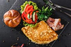 Petit déjeuner, omelette avec le petit pain, lard, prosciutto, salade fraîche et épices sur le conseil en pierre sur la surface n image libre de droits