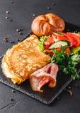 Petit déjeuner, omelette avec le petit pain, lard, prosciutto, salade fraîche et épices sur le conseil en pierre sur la surface n photos libres de droits