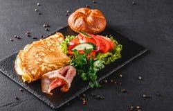 Petit déjeuner, omelette avec le petit pain, lard, prosciutto, salade fraîche et épices sur le conseil en pierre sur la surface n images libres de droits