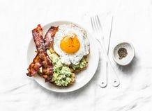 Petit déjeuner ou casse-croûte nutritif sain - pain grillé d'avocat, lard et oeuf au plat sur le fond clair photographie stock