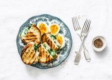 Petit déjeuner ou casse-croûte sain - la ferme bouillie eggs, les épinards, sandwichs grillés à fromage sur le fond clair photo libre de droits