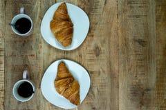 Petit déjeuner ou déjeuner pour deux Croissants d'un plat avec du café photographie stock libre de droits
