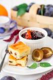 Petit déjeuner : Prune d'amd de gâteau au fromage, de prunes et confiture d'oranges Photographie stock