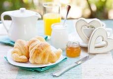 Petit déjeuner romantique avec amour Croissants, café, jus, coeurs en bois Photographie stock