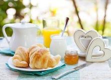 Petit déjeuner romantique avec amour Croissants, café, jus, coeurs en bois Photos stock