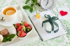 Petit déjeuner romantique dans le lit et cadeau avec amour Image stock
