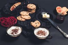 Petit déjeuner romantique deux tasses de café, de cappuccino avec des biscuits de chocolat et de biscuits près des coeurs rouges  Images libres de droits