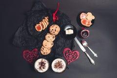 Petit déjeuner romantique deux tasses de café, de cappuccino avec des biscuits de chocolat et de biscuits près des coeurs rouges  Photographie stock