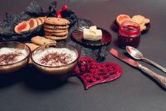 Petit déjeuner romantique deux tasses de café, de cappuccino avec des biscuits de chocolat et de biscuits près des coeurs rouges  Photographie stock libre de droits