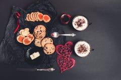 Petit déjeuner romantique deux tasses de café, de cappuccino avec des biscuits de chocolat et de biscuits près des coeurs rouges  Image libre de droits