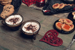 Petit déjeuner romantique deux tasses de café, de cappuccino avec des biscuits de chocolat et de biscuits près des coeurs rouges  Photos stock