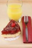 Petit déjeuner romantique servi : verre de jus d'orange et de gâteau au fromage délicieux de cerise Photos stock