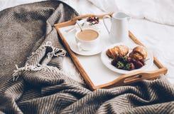 Petit déjeuner romantique traditionnel dans le lit dans la chambre à coucher blanche et beige Photographie stock libre de droits