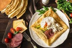 Petit déjeuner rustique : galette de crêpe, oeuf poché, jambon, avocat et fromage Photo libre de droits